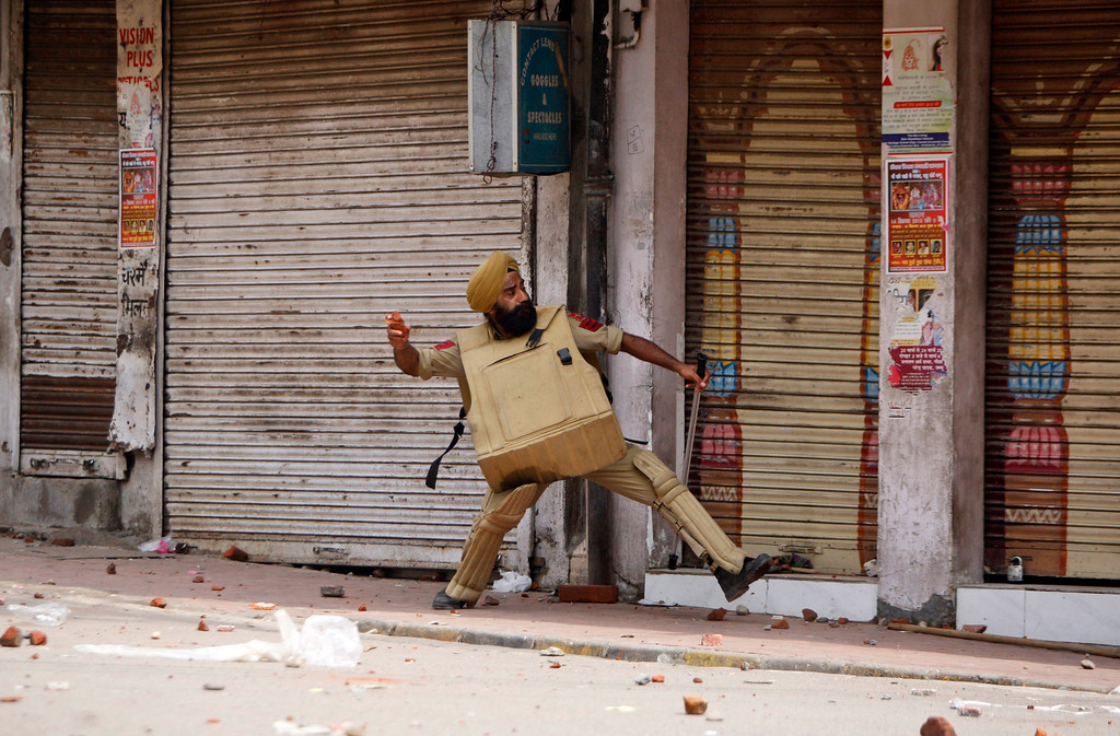 . An Indian policeman throws stones at Hindus protesting against the state government after rival communities clashed in Kishtwar, in Jammu, India, Saturday, Aug. 10, 2013. Indian forces fired warning shots Saturday to enforce a curfew and to push angry people back into their homes in Kishtwar, in the Indian portion of Kashmir where clashes between Muslims and Hindus during Eid celebrations killed at least two people and injured another 24. (AP Photo/Channi Anand)