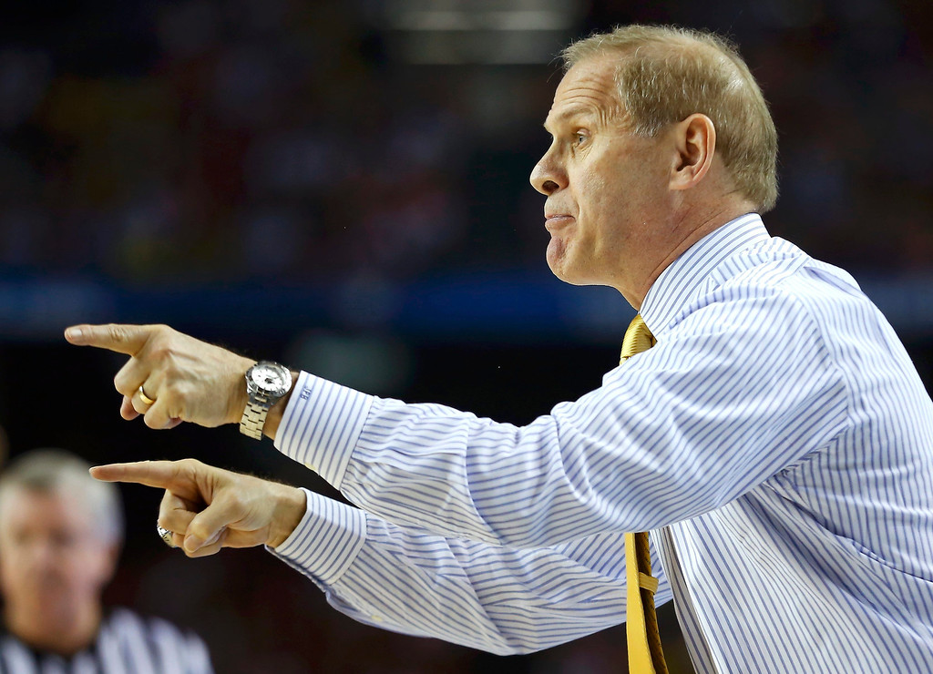 . Michigan Wolverines head coach John Beilein directs his team\'s play against the Louisville Cardinals in the first half of their NCAA men\'s Final Four championship basketball game in Atlanta, Georgia April 8, 2013.  REUTERS/Jeff Haynes