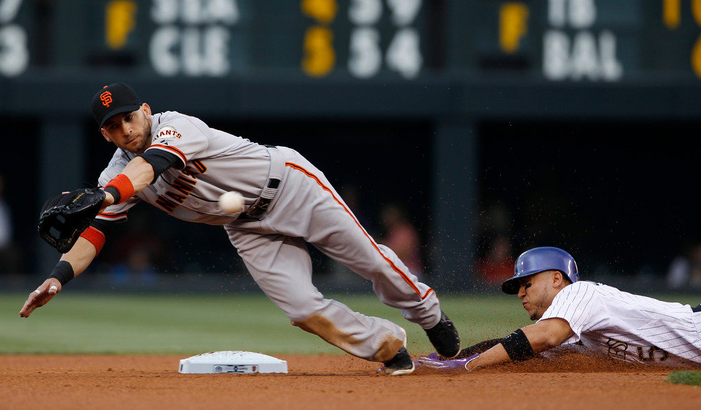 . San Francisco Giants second baseman Marco Scutaro, left, dives to field a throw as Colorado Rockies\' Carlos Gonzalez steals second base in the first inning of a baseball game in Denver, Saturday, May 18, 2013. (AP Photo/David Zalubowski)