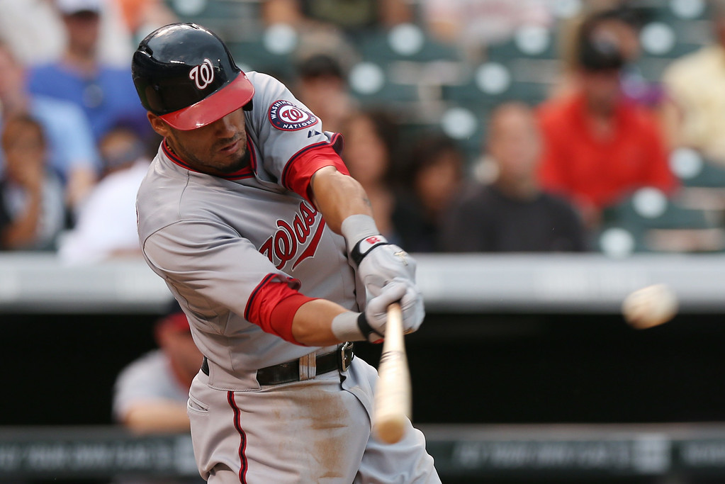 . Washington Nationals\' Ian Desmond hits a single against the Colorado Rockies in the sixth inning of a baseball game in Denver on Wednesday, July 23, 2014. (AP Photo)