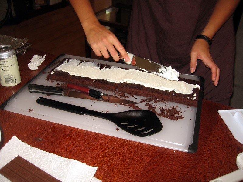 Olivia applies buttercream icing to the brownie base, which helps the fondant stick to the base