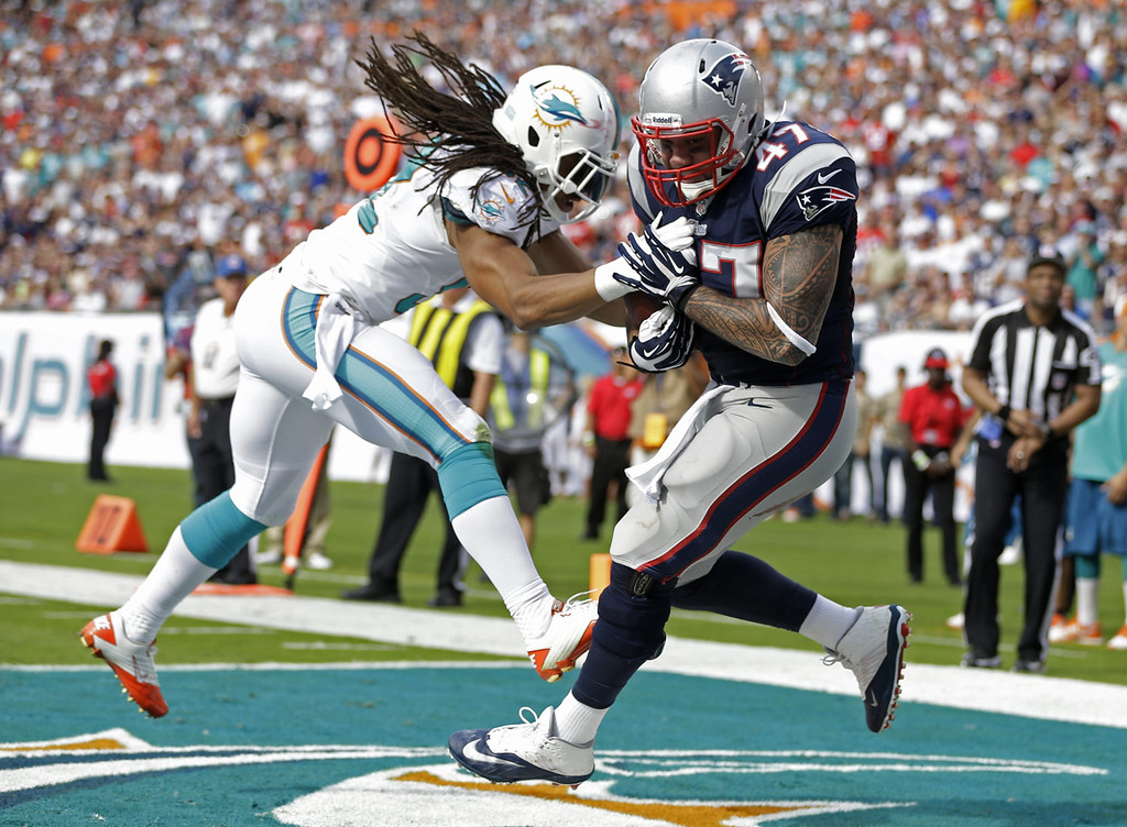 . New England Patriots tight end Michael Hoomanawanui (47) grabs a touchdown pass as Miami Dolphins outside linebacker Philip Wheeler (52) defends during the first half of an NFL football game on Sunday, Dec. 15, 2013, in Miami Gardens, Fla. (AP Photo/Lynne Sladky)