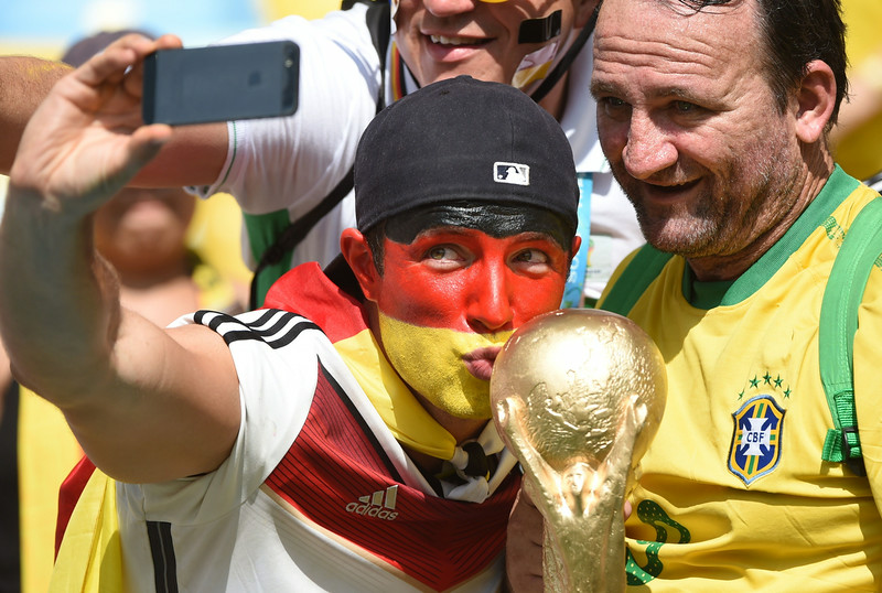 . A German supporter(L) takes a \'selfie\' as he cheers for his team ahead of the quarter-final football match between France and Germany at The Maracana Stadium in Rio de Janeiro on July 4, 2014,during the 2014 FIFA World Cup. (PATRIK STOLLARZ/AFP/Getty Images)