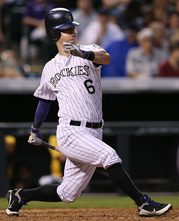 . Colorado Rockies\' Corey Dickerson loses his helmet while swinging at a pitch against the Pittsburgh Pirates in the seventh inning of the Rockies\' 8-1 victory in a baseball game in Denver, Saturday, July 26, 2014. (AP Photo/David Zalubowski)