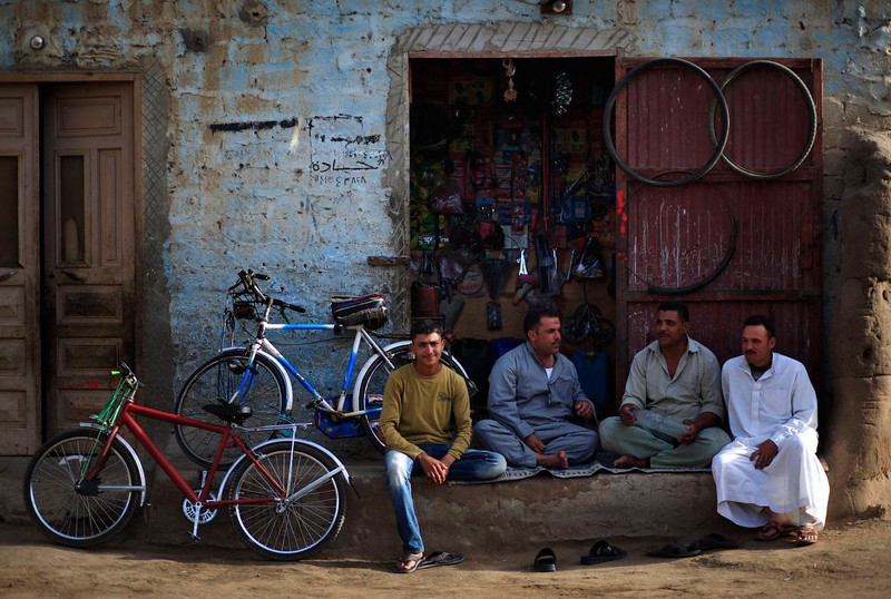 . In this Friday, May 17, 2013 photo, Palestinian refugees sit in front of a bicycle repair shop in Gezirat al-Fadel village, Sharqiya, about 150 kilometers (93 miles) east of Cairo, Egypt.  (AP Photo/Khalil Hamra)