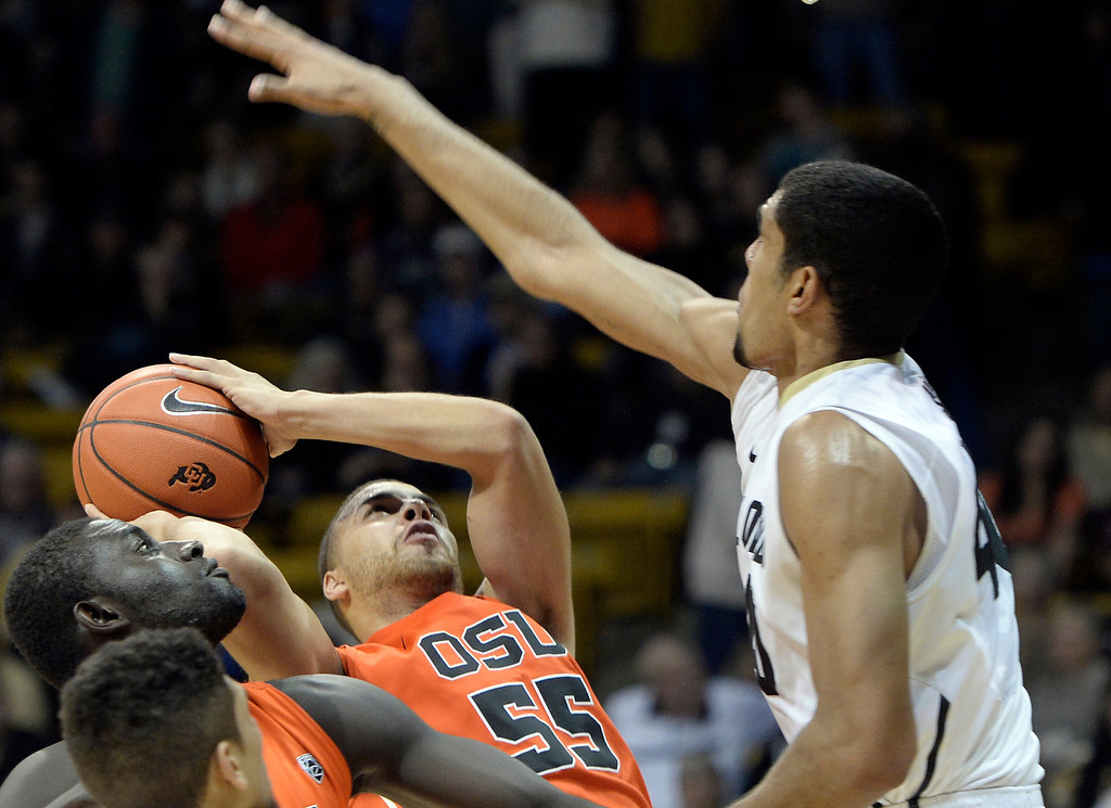 . Oregon\'s Roberto Nelson takes a shot under the arms of Josh Scott during an NCAA game against Colorado on Thursday, Jan. 2, at the Coors Event Center in Boulder.  Jeremy Papasso/ Camera