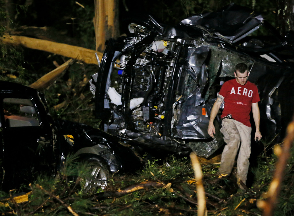 . A searcher walks past the remains of a SUV in Louisville, Miss., early Tuesday morning, April 29, 2014 after a tornado hit the east Mississippi community Monday.  (AP Photo/Rogelio V. Solis)