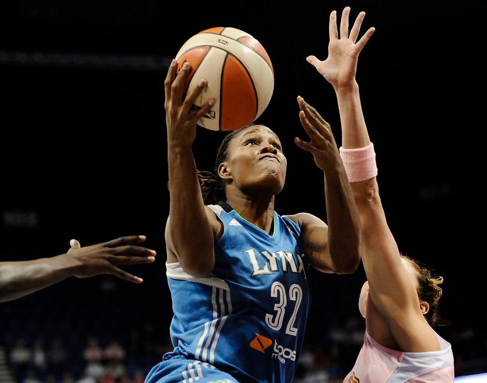 . Minnesota Lynx\'s Rebekkah Brunson drives to the basket while guarded by Connecticut Sun\'s Kelsey Griffin, right, during the first half of a WNBA basketball game in Uncasville, Conn., Thursday, Aug. 22, 2013. Brunson was top scorer for Minnesota with 24 points. Minnesota defeated Connecticut 91-77. (AP Photo/Jessica Hill)