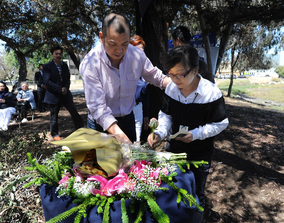 . A couple identified as the parents of Asiana crash victim Ye Mengyuan make an offering of flowers following a prayer ceremony for the Asiana Flight victims put on by the Tzu Chi Foundation in Burlingame, Calif., on Saturday, July 13, 2013. Tzu Chi is an international Buddhist relief organization that began in Taiwan and offers compassionate efforts for charity, medical treatment, education and disaster relief.  (Dan Honda/Bay Area News Group)