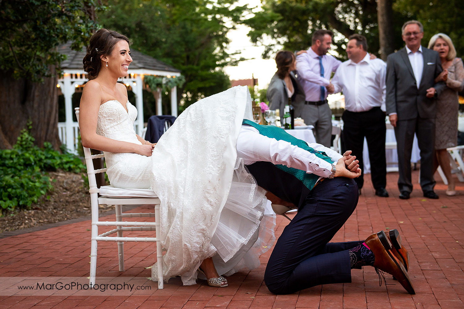 groom under bride's dress removig garter during wedding reception at San Pablo Rockefeller Lodge