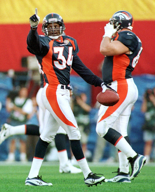 . Caption: Denver Broncos Tyrone Braxton celebrates his first  quarter interception from Green Bay Packers Brett Favre during  Super Bowl XXXII in San Diego CA.  (Karl Gehring/The Denver Post)