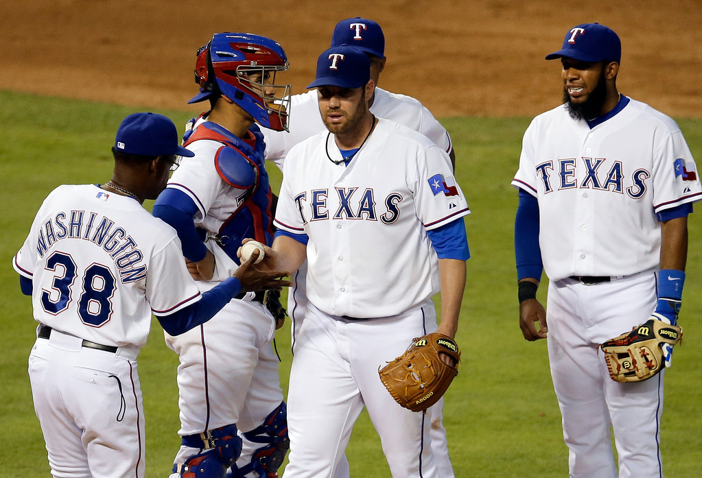 . Texas Rangers manager Ron Washington (38) takes the ball from starting pitcher Colby Lewis as catcher Robinson Chirinos, second from left, Adrian Beltre, rear, and Elvis Andrus stand on the mound in the fourth inning of a baseball game against the Colorado Rockies, Wednesday, May 7, 2014, in Arlington, Texas. (AP Photo/Tony Gutierrez)