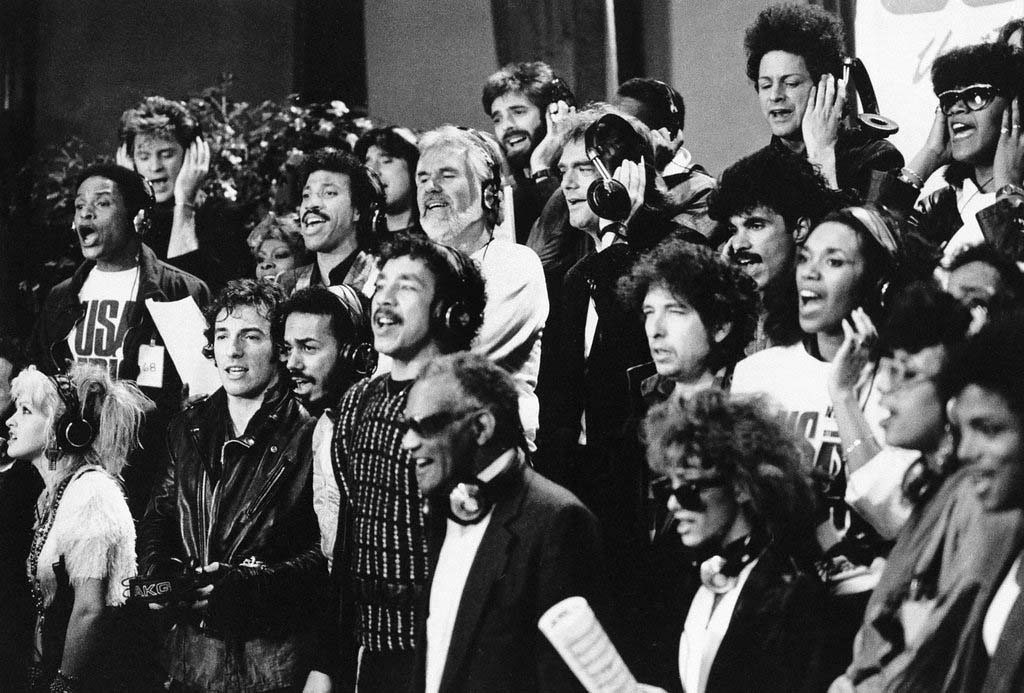 ". Some of a group of 45 music artists calling themselves ""USA For Africa\"" recording \""We Are The World\"" in Los Angeles, Calif.  Jan. 30, 1985. Bottom row, from left; Cyndi Lauper, Bruce Springsteen, James Ingram, Smokey Robinson, Ray Charles, Sheila E., June Pointer, Randy Jackson. Middle row, from left; Al Jarreau, Dionne Warwick, Lionel Richie, Kenny Rogers, Huey Lewis, Bob Dylan, John Oates, Ruth Pointer. Top row, from left; Daryl Hall, Steve Perry, Kenny Loggins, Jeffrey Osborne, Lindsay Buckingham, and Anita Pointer.  (AP Photo)"