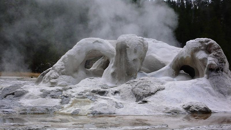 """Grotto Geyser steam between eruptions. The cause of the odly shaped """"cone"""" is not known, but it may be from trees encased in the solidfied spray from the geyser."""