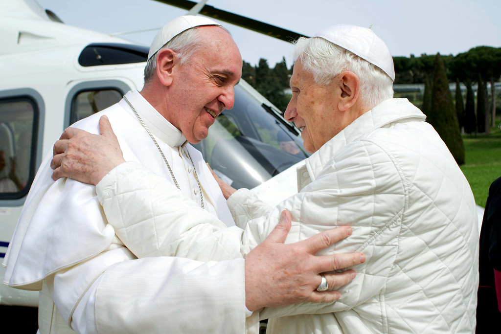 """. In this photo provided by the Vatican paper L\'Osservatore Romano, Pope Francis meets Pope emeritus Benedict XVI in Castel Gandolfo Saturday, March 23, 2013. Pope Francis had traveled to Castel Gandolfo to have lunch with his predecessor Benedict XVI in a historic and potentially problematic melding of the papacies that has never before confronted the Catholic Church. The Vatican said the two popes embraced on the helipad. In the chapel where they prayed together, Benedict offered Francis the traditional kneeler used by the pope. Francis refused to take it alone, saying \""""We\'re brothers,\"""" and the two prayed together on the same one. (AP Photo/Osservatore Romano, File)"""