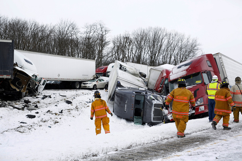 . Emergency personnel work at the scene of a crash near Fredericksburg, Pa., Saturday, Feb. 13, 2016. State police say the pileup has closed Interstate 78 in central Pennsylvania. (Daniel Zampogna/PennLive.com via AP)