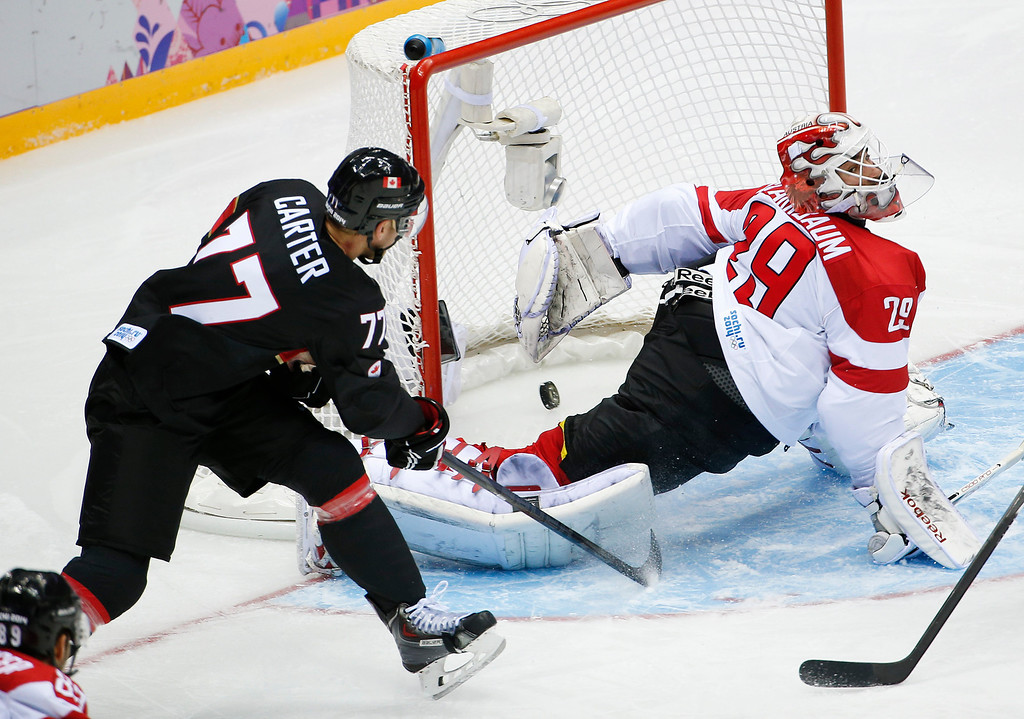 . Canada forward Jeff Carter shoots and scores against Austria goaltender Bernhard Starkbaum in the second period of a men\'s ice hockey game at the 2014 Winter Olympics, Friday, Feb. 14, 2014, in Sochi, Russia. (AP Photo/Julio Cortez)