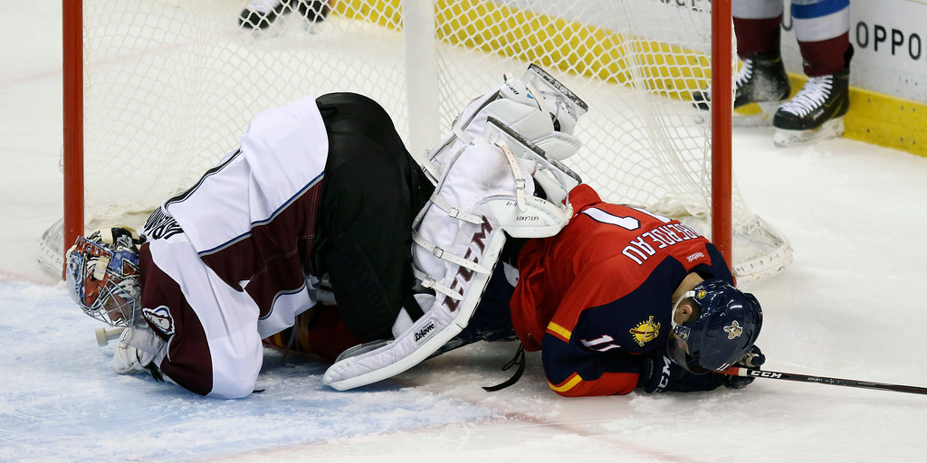 . Florida Panthers\' Jonathan Huberdeau (11) slides into Colorado Avalanche goalie Seymon Varlamov (1) and knocks him to the ice during the second period of an NHL hockey game, Thursday, Jan. 15, 2015 in Sunrise, Fla. (AP Photo/J Pat Carter)