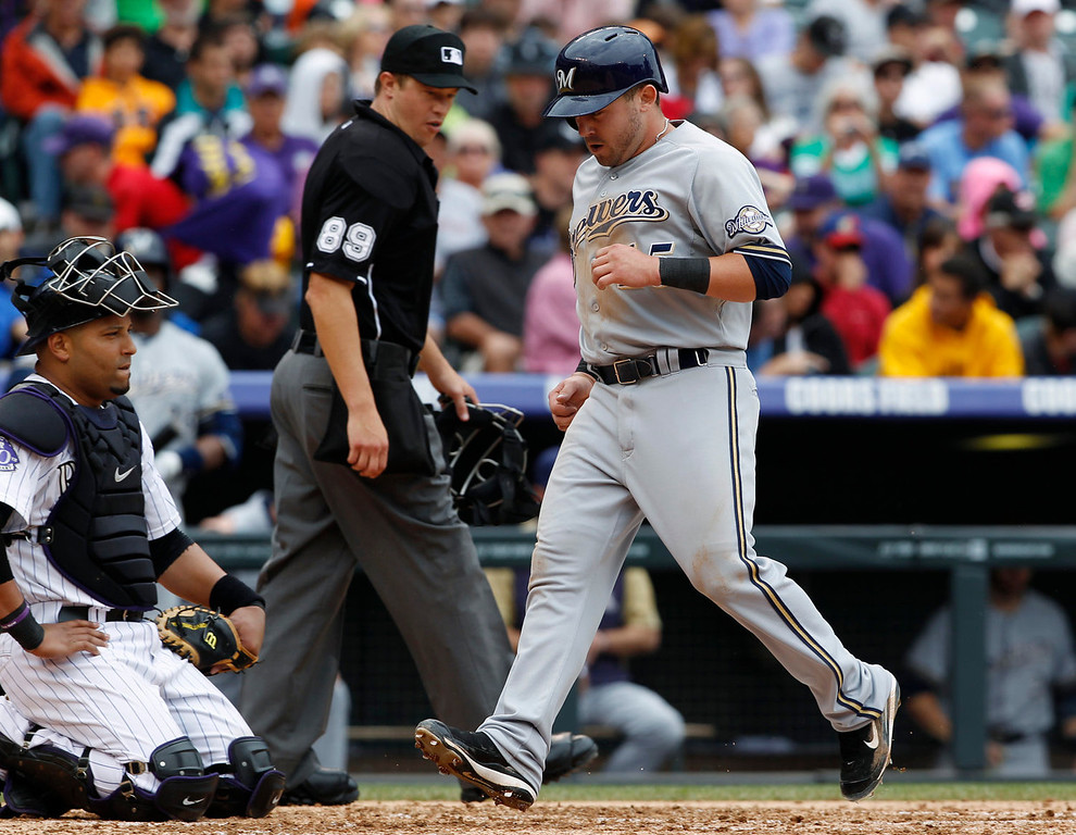 . Milwaukee Brewers\' Caleb Gindl, right, scores on a single by Jeff Bianchi as Colorado Rockies catcher Yorvit Torrealba, left, and home plate umpire Cory Blaser looks on in the fourth inning of a baseball game in Denver, Sunday, July 28, 2013. (AP Photo/David Zalubowski)