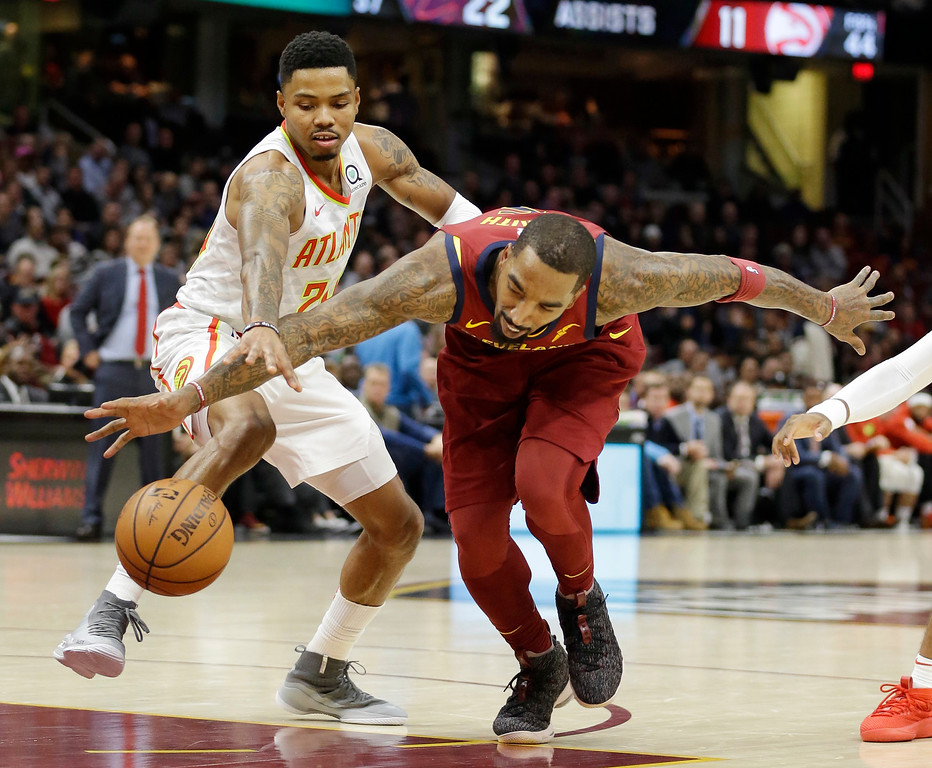 . Atlanta Hawks\' Kent Bazemore, left, and Cleveland Cavaliers\' JR Smith battle for a loose ball in the second half of an NBA basketball game, Tuesday, Dec. 12, 2017, in Cleveland. The Cavaliers won 123-114. (AP Photo/Tony Dejak)