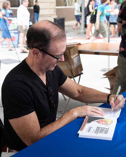 Mike Luckovich, AJC Cartoonist, signs his latest book at the Decatur Book Festival