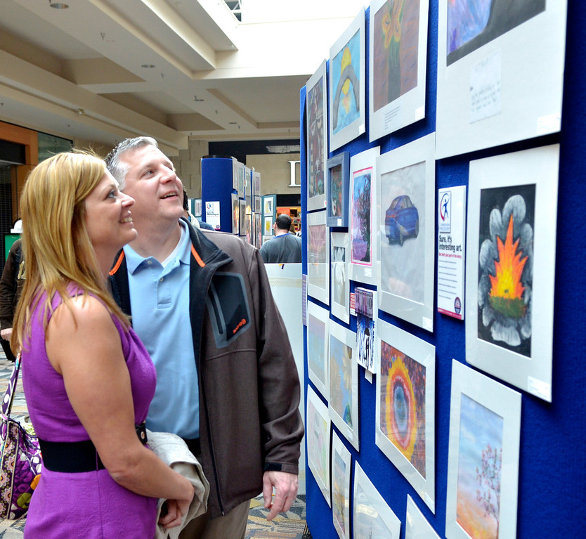 """. Jeff Forman/JForman@News-Herald.com Christine and Jason Lakomiak, of Concord Township, check out the artwork on display at \""""Expressions of Recovery\"""" exhibit at the Great Lakes Mall. The show is sponsored by the Lake County ADAMHS Board."""