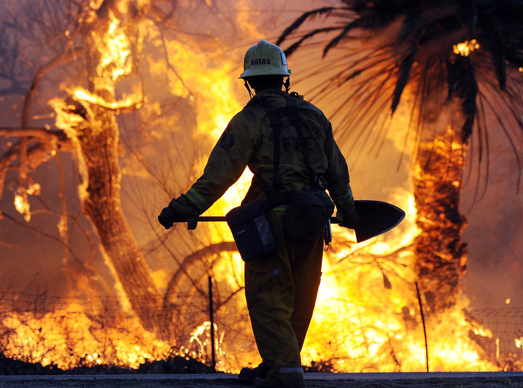 . A firefighter waits for flames to die down next to the Louis Robidoux Nature Center in the Jurupa Valley on Feb. 28, 2013. As of 7 p.m. approximately 50 acres had burned. (Will Lester/Inland Valley Daily Bulletin)