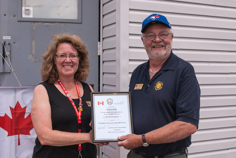 Jeanette Rooke receives a certificate of appreciation from Bob Jones of the Optimist Club of East Williams for hosting riders from their charity ride.