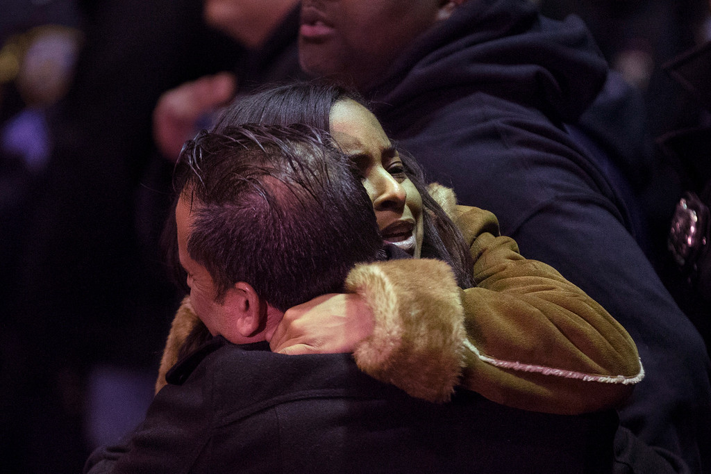 . Mourners gather before the bodies of two fallen NYPD police officers are transported from Woodhull Medical Center, Saturday, Dec. 20, 2014, in New York. An armed man walked up to two New York Police Department officers sitting inside a patrol car and opened fire Saturday afternoon, killing one and critically wounding a second before running into a nearby subway station and committing suicide, police said. (AP Photo/John Minchillo)