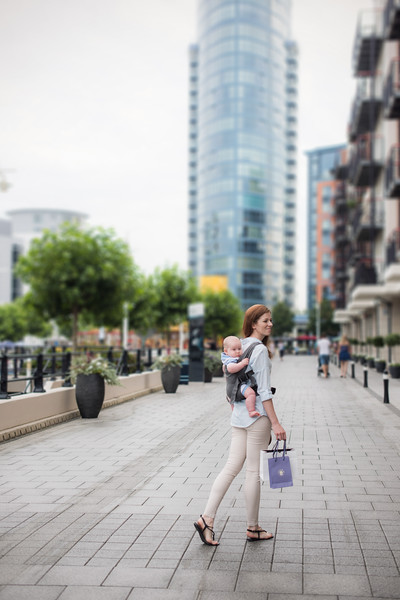 Izmi_Baby_Carrier_Mid_Grey_Lifestyle_Back_Carry_Mum_Walking_In_City_Wide_Angleps.jpg