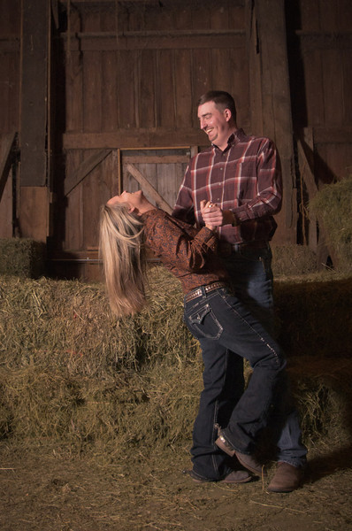 Couple share a fun moment in a barn during winter engagement photos near Severson Dells in Rockford, IL