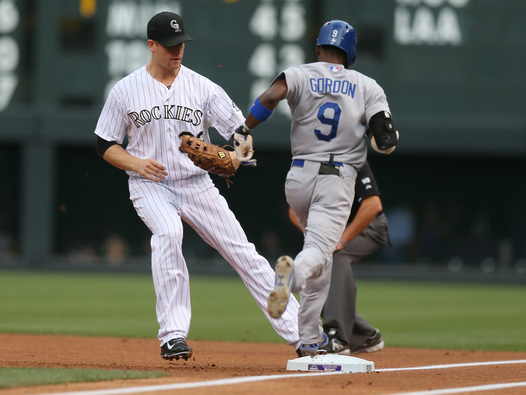 . Colorado Rockies first baseman Justin Morneau, left, touches first base to put out Los Angeles Dodgers\' Dee Gordon after fielding a ground ball off Gordon\'s bat in the first inning of a baseball game in Denver, Thursday, July 3, 2014. (AP Photo/David Zalubowski)