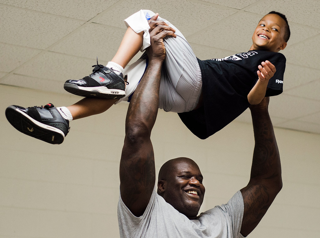 . NBA legend Shaquille O\'Neal lifts Jaedan Hanley, 9, of Gardner, while taking photographs with Dan McHugh Photography, out of Kingston, during the inaugural Rolle\'s All-Star Basketball Clinic held at Gardner High School on Saturday, August 5, 2017. SENTINEL & ENTERPRISE / Ashley Green