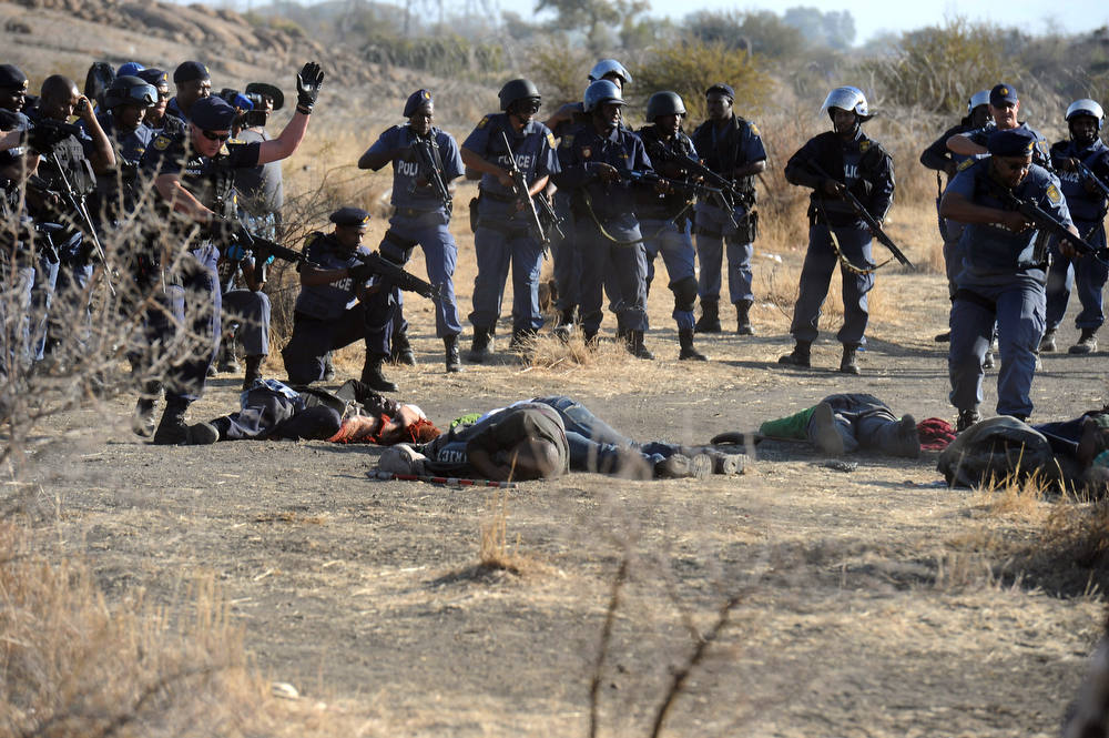 Description of . Police surround fallen miners after they opened fire during clashes near a platinum mine in Marikana on August 16, 2012. Hundreds of workers armed with machetes, sticks and metal rods had gathered on a hillside near the mine, defying police orders to disperse. Several people were lying on the ground, some bleeding from wounds, after the crowd fled, according to an AFP reporter. AFP PHOTO-/AFP/Getty Images