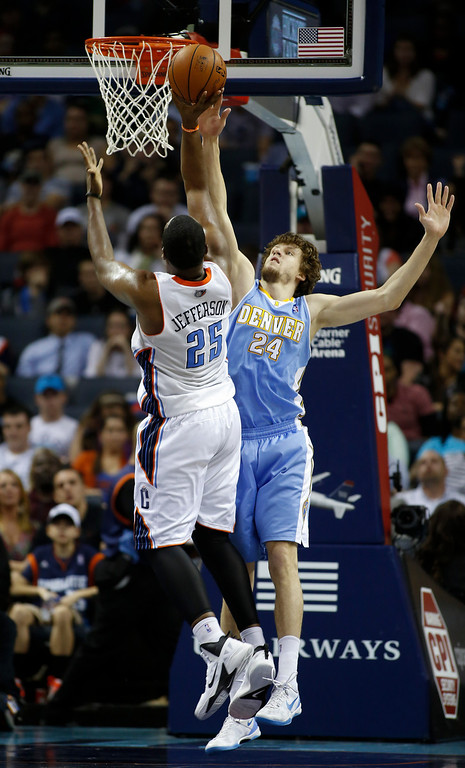 . Charlotte Bobcats center Al Jefferson, left, shoots over Denver Nuggets forward Jan Vesely, of the Czech Republic, in the second half of an NBA basketball game in Charlotte, N.C., Monday, March 10, 2014. Charlotte won 105-98. (AP Photo/Nell Redmond)