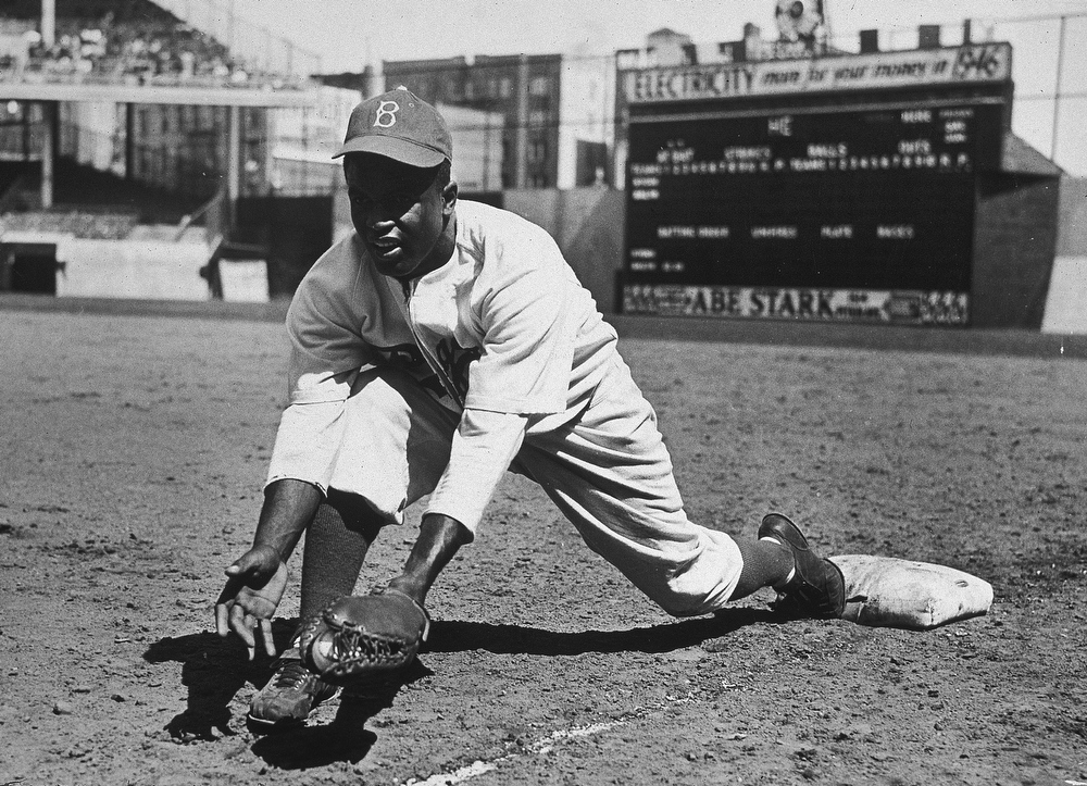 Description of . American baseball player Jackie Robinson (1919 - 1972) grounds a ball at first place while warming up for an exhibition game against the New York Yankees, Ebbets Field, NYC, 1950s.  (Photo by Hulton|Archive/Getty Images)