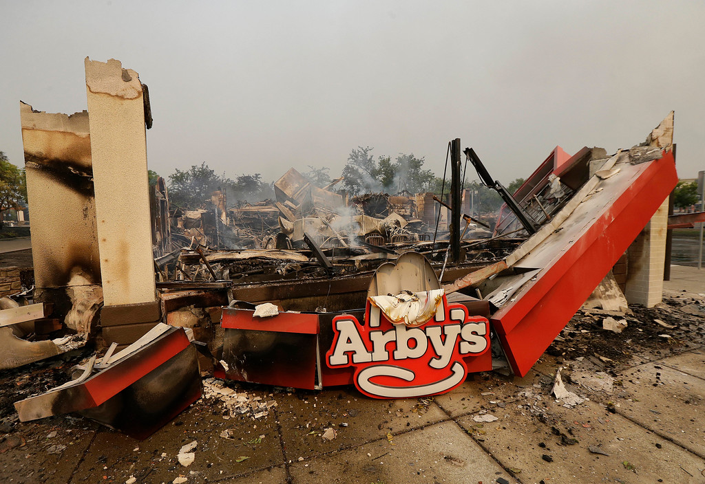 . Smoke rises from an Arby\'s Restaurant that was destroyed by a wildfire in Santa Rosa, Calif., Monday, Oct. 9, 2017. Wildfires whipped by powerful winds swept through Northern California early Monday, sending residents on a headlong flight to safety through smoke and flames as homes burned. (AP Photo/Jeff Chiu)