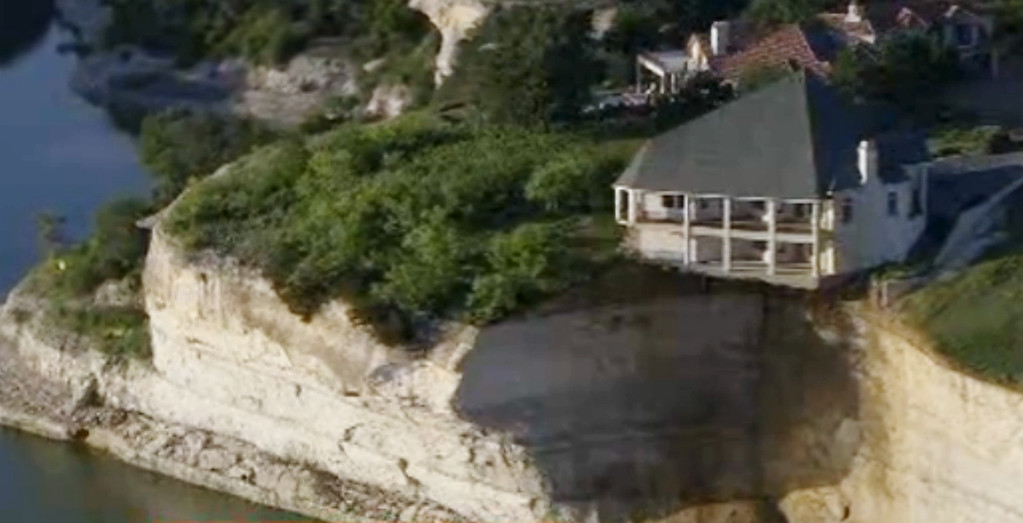 . In this image taken from Tuesday, June 10, 2014 video provided by WFAA-TV, a luxury house teeters on a cliff about 75 feet above Lake Whitney in Whitney, Texas. WFAA-TV reported Wednesday, June 11, 2014 that the house has been condemned and the owners evacuated about two weeks ago. (AP Photo/WFAA.com)