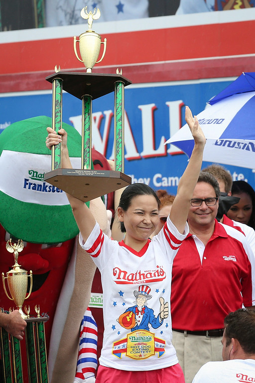 . Sonya Thomas raises her trophy after placing second at the Nathan\'s Famous Fourth of July International Hot Dog Eating contest at Coney Island, Friday, July 4, 2014, in New York. Miki Sudo dethroned Thomas, the reigning champion, by eating 34 hot dogs and buns. (AP Photo/John Minchillo)