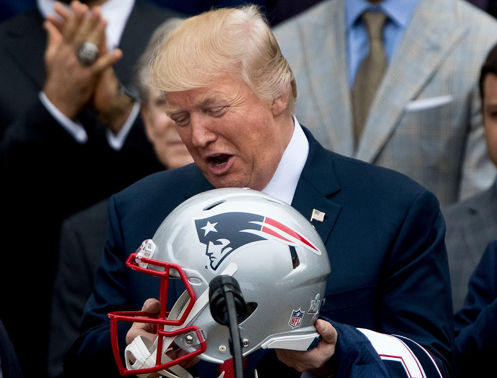 . President Donald Trump is presented with a New England Patriots football helmet by Patriots head coach Bill Belichick and New England Patriots owner Robert Kraft during a ceremony on the South Lawn of the White House in Washington, Wednesday, April 19, 2017, where the president honored the Super Bowl Champion New England Patriots for their Super Bowl LI victory. (AP Photo/Andrew Harnik)