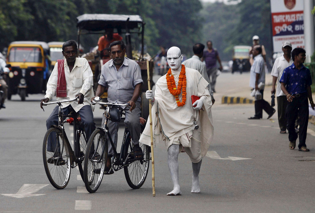 . An Indian man dressed as Mahatma Gandhi prepares to cross a busy road as he returns after attending a function to mark Gandhi\'s birth anniversary in Bhubaneswar, India, Wednesday, Oct. 2, 2013. (AP Photo/Biswaranjan Rout)