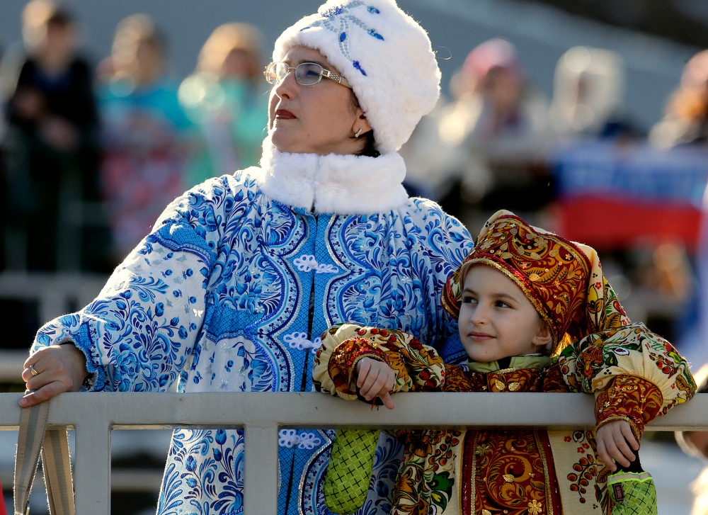 . Spectators watch the women\'s skeleton competition at the 2014 Winter Olympics, Thursday, Feb. 13, 2014, in Krasnaya Polyana, Russia. (AP  Photo/Charlie Riedel)