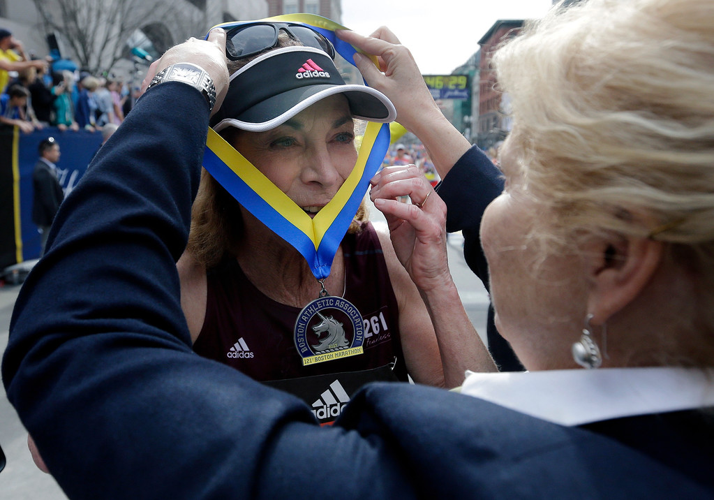 . Kathrine Switzer,  the first official woman entrant in the Boston Marathon 50 years ago, receives her medal from Joann Flaminio, right, of the Boston Athletic Association,after finishing the marathon Monday, April 17, 2017, in Boston. (AP Photo/Elise Amendola)