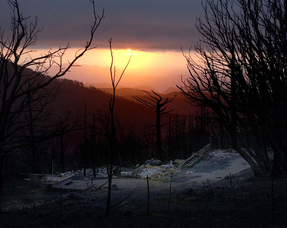 . The charred remains of mountain home in Cuyamaca, Calif. is seen as the sun dips below a bank of fog Friday, Oct 31, 2003. Cool damp weather is aiding firefighters in controlling the 272,000 acre Cedar fire east of San Diego. (AP Photo/Charlie Riedel)
