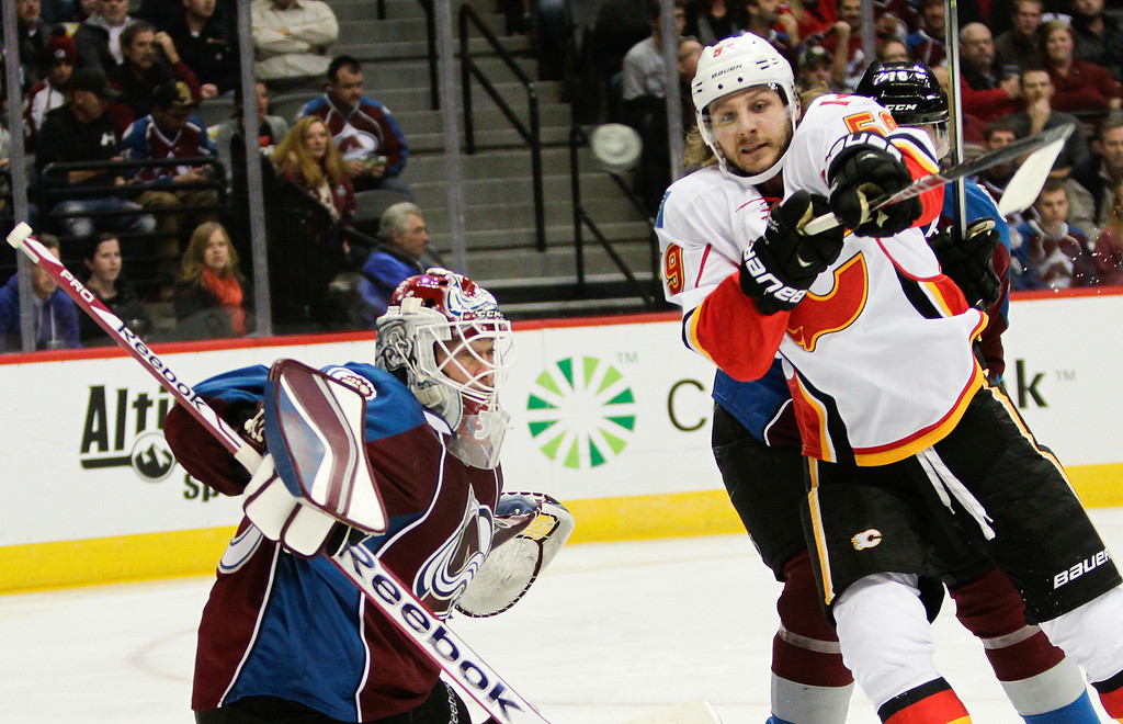 . Calgary Flames\' Max Reinhart, right, tries to slap the puck out of midair with Colorado Avalanche goalie Jean-Sebastien Giguere, left, watching during the second period of an NHL hockey game on Friday, Nov. 8, 2013, in Denver. (AP Photo/Barry Gutierrez)