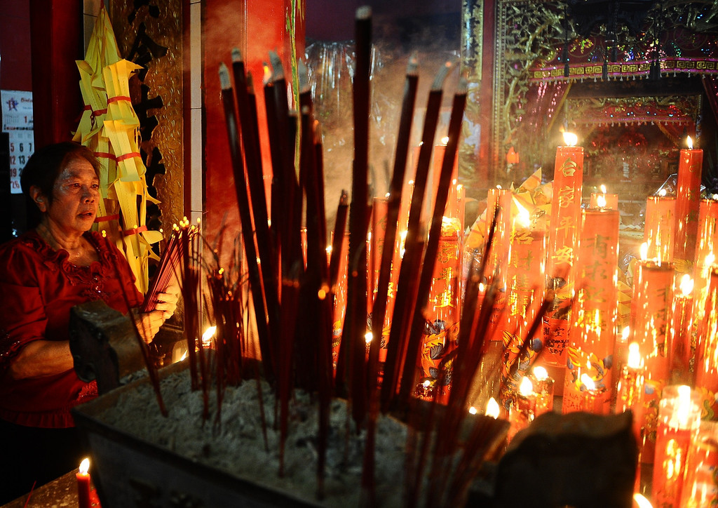 . A woman prays holding incense sticks at Hong San Ko Tee Temple during Chinese New year Celebrations on January 31, 2014 in Surabaya, Indonesia. Thousands gathered today to celebrate the Chinese New Year and welcome the Year of the Horse, with new year\'s day falling on January 31st.  (Photo by Robertus Pudyanto/Getty Images)