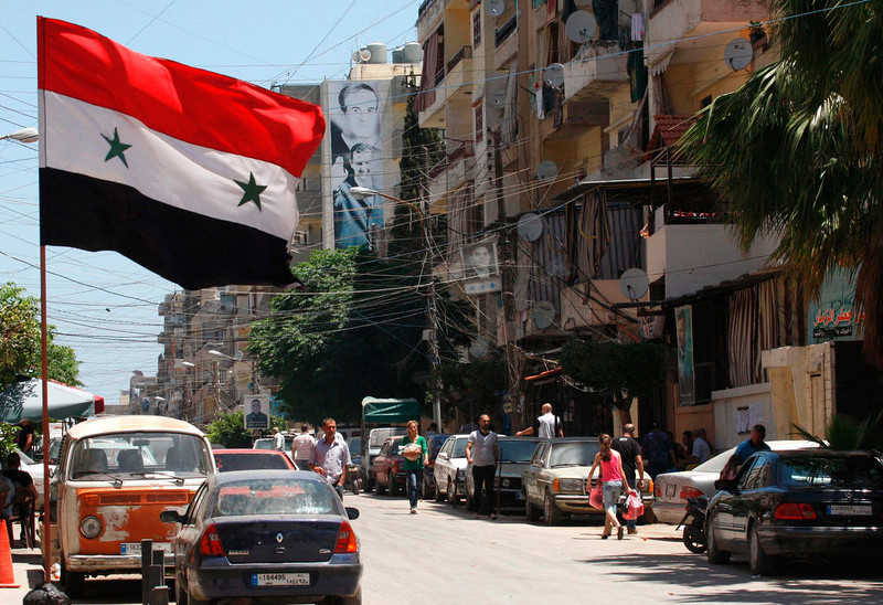 . The Syrian national flag flutters as pictures of Syria\'s President Bashar al-Assad along with his father Syria\'s late president Hafez al-Assad are seen on a wall of a building in the Alawite Jabal Mohsen neighborhood in the port city of Tripoli, northern Lebanon June 5, 2013. Twenty nine people were killed last month in the deadliest fighting yet between gunmen sympathetic to the uprising against Bashar al-Assad and Alawite supporters of the Syrian president. REUTERS/Stringer