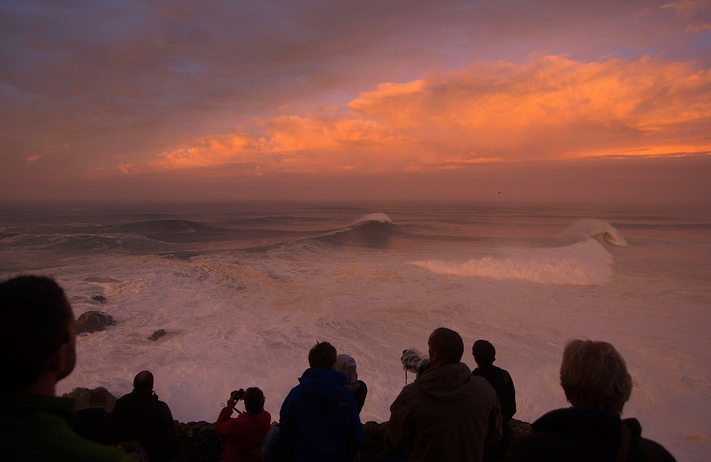 . Photographers watch the sunrise at the Praia do Norte, north beach, at the fishing village of Nazare in Portugal\'s Atlantic coast Monday, Oct. 28 2013. On Monday Brazilian suffer Carlos Burle surfed a wave here that surf media suggest could be the biggest wave ever surfed and Maya Gabeira, also from Brazil, nearly drowned and was taken to hospital with a broken ankle after falling in a big wave. (AP Photo/Miguel Barreira)