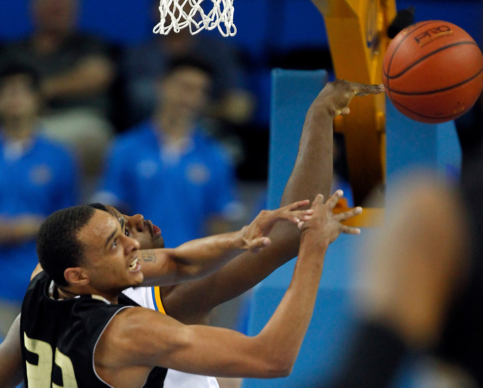 . Oakland forward Tommie McCune, left, battles UCLA center Tony Parker for a rebound in the second half of their NCAA college basketball game Tuesday, Nov. 12, 2013, in Los Angeles. UCLA won the game 91-60.  (AP Photo/Alex Gallardo)