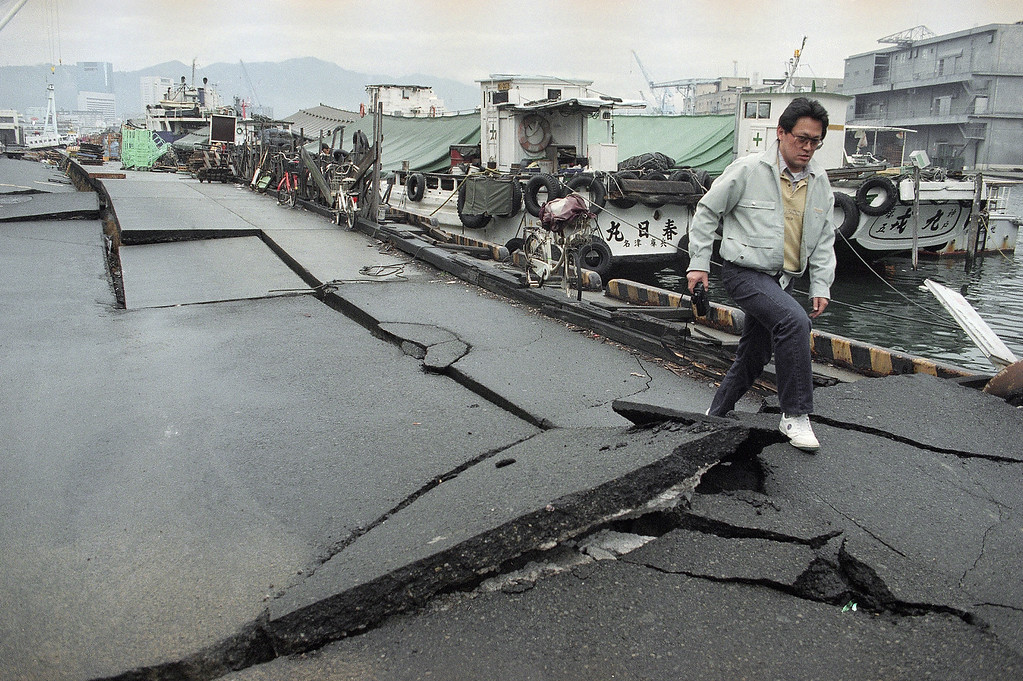 . A pedestrian makes his way over the quake-damaged pier at the Kobe Port, Jan. 22, 1995. The death toll from the 7.2-magnitude quake, Jan., 17, 1995, Japan\'s deadliest in more than 70 years, was at 4,914, and hopes were fading for others still listed as missing. More than 25,500 were injured. (AP Photo/Itsuo Inouye)